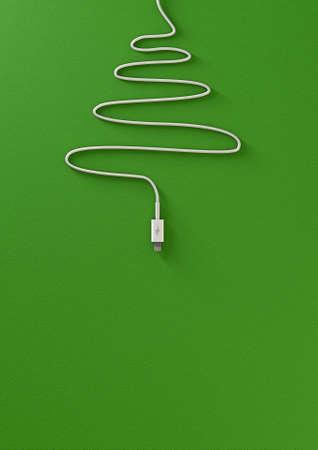 fiestas electronicas: Un cargador de teléfono móvil envuelto en la forma de un árbol de Navidad en un fondo verde aislado con el espacio de la copia
