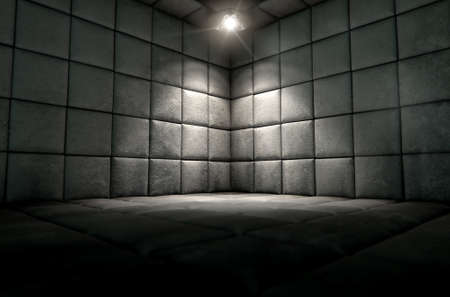 A dark dirty white padded cell in a mental hospital with a corner lit by a single spotlight