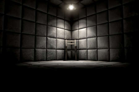 A dark dirty white padded cell in a mental hospital with an empty chair in the corner lit by a single spotlight Stock fotó - 51285081
