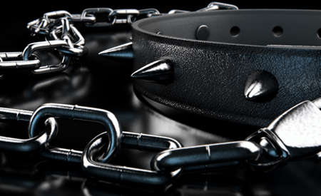 sadism: A black leather dog collar with metal spiked studs attached to a metal chain isolated on a dark studio background