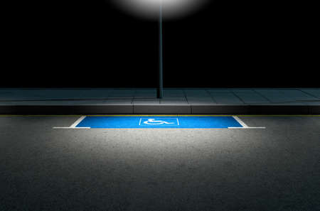 sidewalk: A section of a tarmac road with an empty demarcated paraplegic parking area at night lit by a street pole light