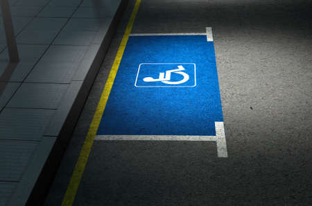 paraplegic: A section of a tarmac road with an empty demarcated paraplegic parking area at night lit by a street pole light