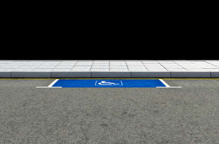 paraplegic: A section of a tarmac road with an empty demarcated paraplegic parking area