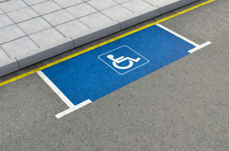 asphalt: A section of a tarmac road with an empty demarcated paraplegic parking area