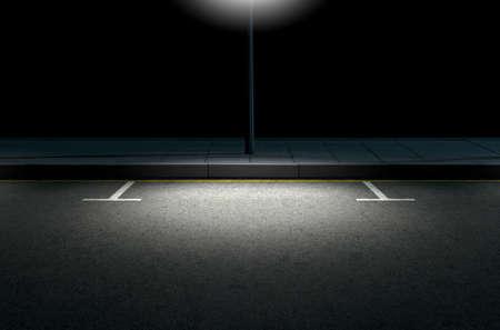 Una sección de una carretera asfaltada con zonas de aparcamiento delimitadas al lado de un pavimento iluminado por un poste de la calle en la noche Foto de archivo