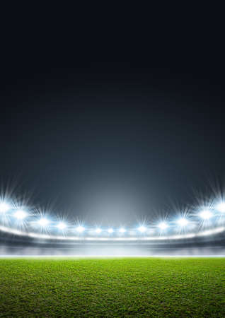 A generic stadium with an unmarked green grass pitch at night under illuminated floodlights Stock Photo