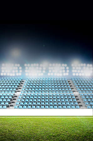 unmarked: A generic stadium with an unmarked green grass pitch at night under illuminated floodlights Stock Photo