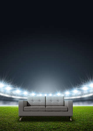 floodlit: A modern sofa in the middle of a generic stadium with an unmarked green grass pitch at night under illuminated floodlights
