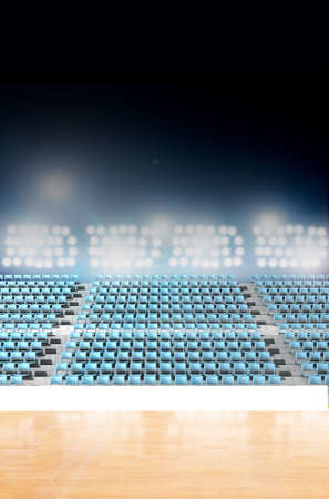 floodlit: A generic indoor stadium with an unmarked wooden court at night under illuminated floodlights Stock Photo