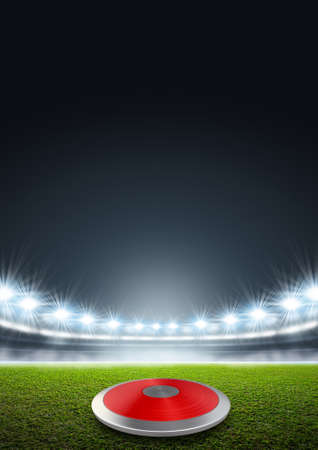 unmarked: A discus in a generic stadium resting on an unmarked green grass pitch at night under illuminated floodlights Stock Photo