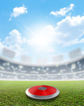 discus: A discus in a generic sports  stadium resting on a marked green grass pitch in the daytime under a blue sky