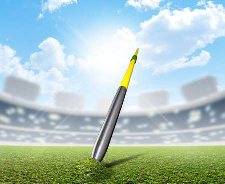 unmarked: A javelin pegged into the turf of a generic sports  stadium with a marked green grass pitch in the daytime under a blue sky Stock Photo