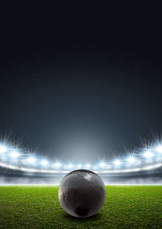 unmarked: A shotput ball in a generic stadium resting on an unmarked green grass pitch at night under illuminated floodlights Stock Photo