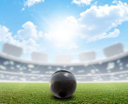 unmarked: A shotput ball in a generic sports  stadium resting on a marked green grass pitch in the daytime under a blue sky