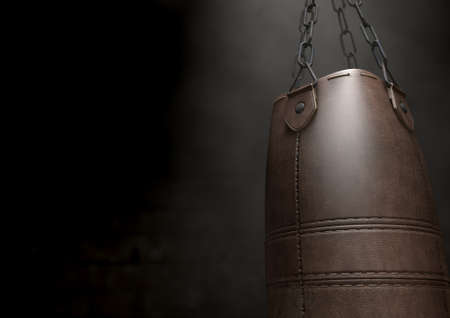 punching bag: A 3D render of an old worn vintage leather punching bag in a room dark room lit by an ethereal spotlight Stock Photo
