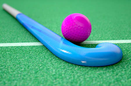 A 3D rendering of a hockey stick and ball on green artificial grass in the daytime