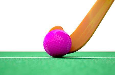 hockey cesped: Una representación 3D de un palo de hockey y la pelota en el césped artificial verde durante el día