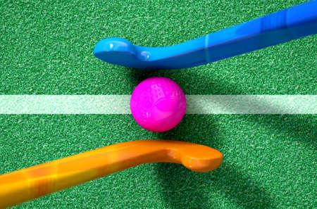 Een 3D-rendering van twee hockeysticks stadning tegenover elkaar over een bal op groen kunstgras in de dag Stockfoto