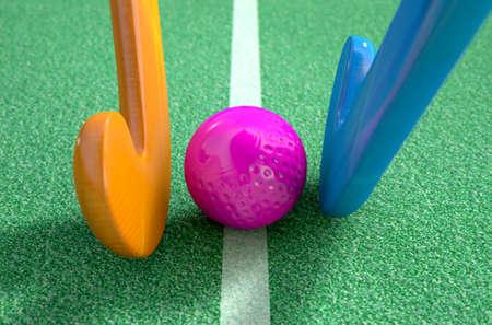 hockey cesped: Una representación 3D de dos palos de hockey stadning uno frente al otro sobre una pelota en el césped artificial verde durante el día