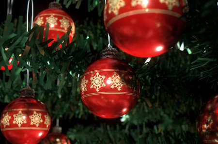 fake christmas tree: A 3D render of a closeup of red christmas baubles decorated with fine ornate snowflake patterns hanging in a fake green christmas tree