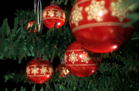A 3D render of a closeup of red christmas baubles decorated with fine ornate snowflake patterns hanging in a fake green christmas tree