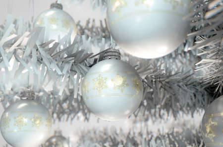burnished: A 3D render of a closeup of white christmas baubles decorated with fine ornate snowflake patterns hanging in a fake white christmas tree