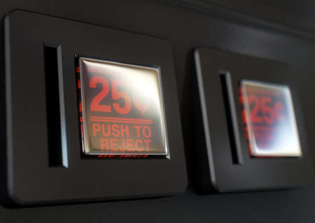 25 cents: A 3D render of a closeup of a coin slot panel from a vintage arcade game machine with entry and exit slots and  button on an isolated background