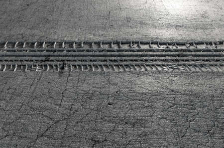 space weather tire: A 3D render of car tire track indenting a cracked grey surface to produce tracks with copy space