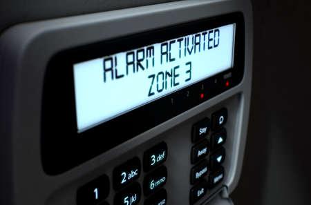 Una representación 3D de un teclado del panel de acceso de seguridad a casa con botones y una pantalla iluminada mostrando la ruptura o fallo de seguridad