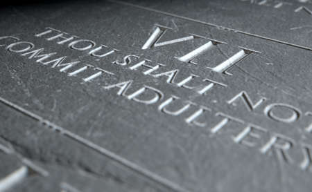 highlighting: A 3D render of closeup of the ten commandments etched in a stone tablet highlighting the seventh Stock Photo