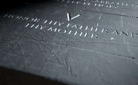 honour: A 3D render of closeup of the ten commandments etched in a stone tablet highlighting the fifth Stock Photo