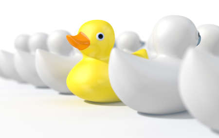 A non-conformist depiction of a yellow rubber bath duck swimming against the flow of white rubber ducks on an isolated white studio background. 3D render