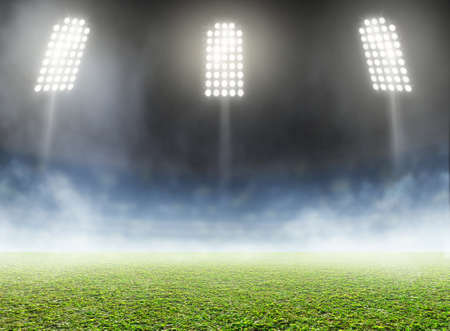 A generic outdoor stadium with an unmarked green grass pitch with an eerie mist at night under illuminated floodlights - 3D render