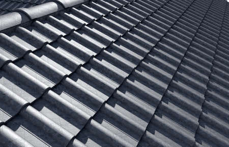capping: Top view of an intersecting corner of a roof tiled in grey clay tiles and a runoff valley - 3D render