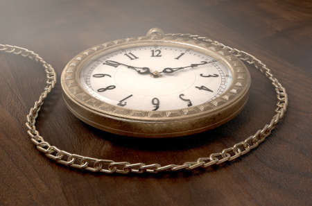 embellished: A closeup of an intricate gold antique pocket watch attached to a chain on a wooden surface background - 3D render Stock Photo