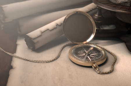 vintage scrolls: A table layout of a vintage pocket compass old scrolls and a world globe model - 3D render Stock Photo