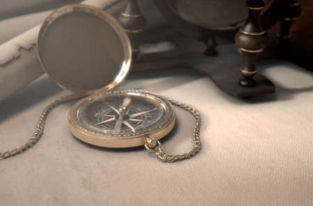 bygone: A table layout of a vintage pocket compass old scrolls and a world globe model - 3D render Stock Photo