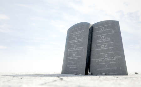 Two stone tablets with the ten commandments inscribed on them standing in brown desert sand infront of a blue sky - 3D render Banco de Imagens