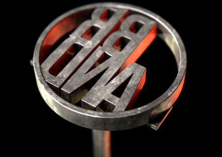 proprietary: A metal cattle branding iron with the word brand as the marking area on an isolated dark surface - 3D render