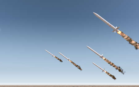 A row of intercontinental ballistic missiles launching in a desert on a blue sky backgrund - 3D render 스톡 콘텐츠