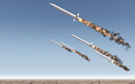 onslaught: A row of intercontinental ballistic missiles launching in a desert on a blue sky backgrund - 3D render Stock Photo