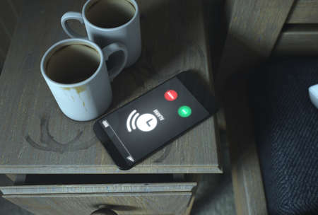 worn: A real life concept scene showing a bed side table with dirty coffee mugs and a generic illuminated smartphone with someone calling at night - 3D Render Stock Photo