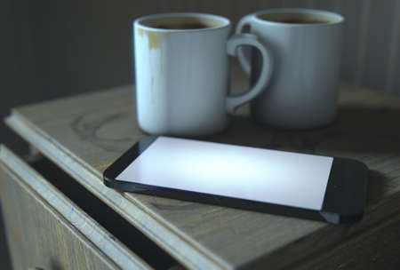 worn: A real life concept scene showing a bed side table with dirty coffee mugs and a generic illuminated smartphone at night - 3D Render Stock Photo