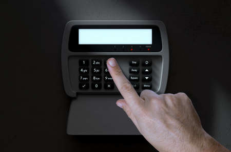 numeric: A male hand pressing a button of a home security control panel at night - 3D render Stock Photo