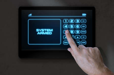 intrusion: A male hand pressing the screen of a home security control panel with words that read system armed - 3D render