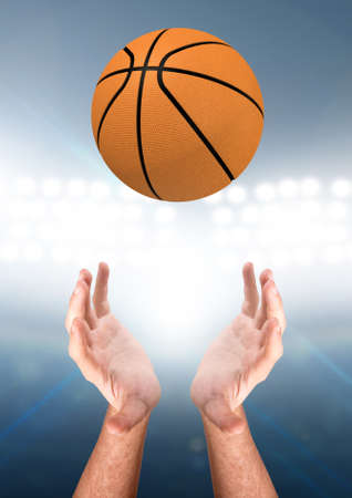 A pair of male hands reaching upwards to catch a basketball on a floodlit stadium background - 3D render