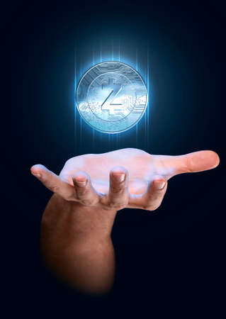 A male hand conjuring up a floating blue zcash cryptocurrency hologram in physical coin form on a dark studio background Stock Photo