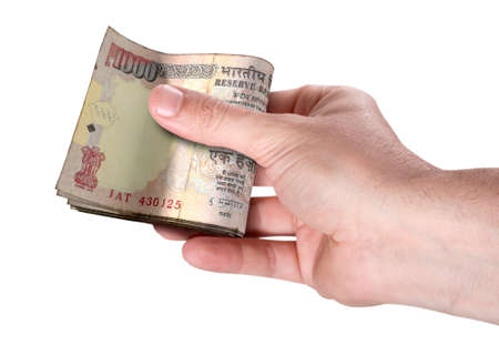 A male hand handing over a wad of folded indian rupee bank notes on an isolated background