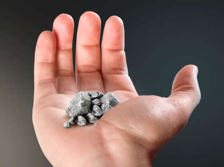 An open male hand revealing a small pile of silver nuggets in the palm on an isolated dark background
