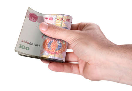A male hand handing over a wad of chinese yuan folded bank notes on an isolated background Stock Photo